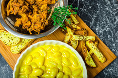 Curry gnocchi with bhajjis and roasted potato. On wood plate royalty free stock photos