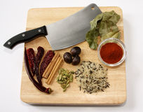 Curry ingredients. Wooden chopping board with meat cleaver, rice and a selection of spices Royalty Free Stock Image