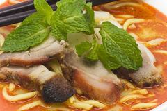 Curry Laksa Noodle. Is a hot and spicy noodle soup serve with barbeque pork and fish cake top with mint leaves. This is a very popular meal you can order in Royalty Free Stock Images