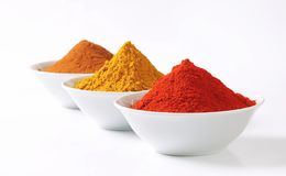 Curry powder, paprika and ground cinnamon Stock Photos