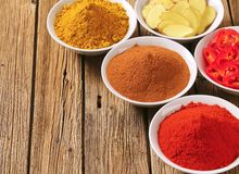Curry powder, paprika,  ground cinnamon, sliced ginger root and Royalty Free Stock Images