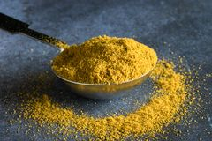 Curry powder in a teaspoon. A teaspoon of curry powder spilling onto a blue grey surface Royalty Free Stock Images