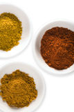 Curry powder, turmeric and cayenne isolated Stock Photos