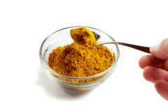 Curry seasoning. Curry powder in a glass bowl with a spoon in an hand Royalty Free Stock Photos