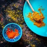 Curry und roter Pfeffer auf einer blauen Platte Stockfotos