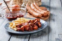 Currywurst alemán tradicional - pedazos de salchicha con la salsa de curry fotos de archivo