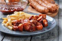 Currywurst alemão tradicional - partes de salsicha com molho de caril imagens de stock royalty free