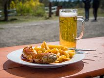 Currywurst and beer. Traditional german curry wurst and beer served outdoors Royalty Free Stock Photography