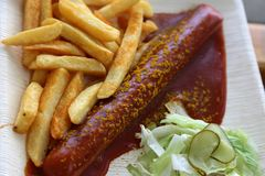 Currywurst curry sausage with french fries and cucumber salad and tomato ketchup. Delicious curry sausage with spices on elegant plate flat lay food fast food Stock Photography