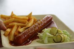 Currywurst curry sausage with french fries and cucumber salad and tomato ketchup. Delicious curry sausage with spices on elegant plate flat lay food fast food Stock Photo