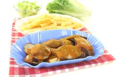 Currywurst with french fries on a napkin Stock Photography