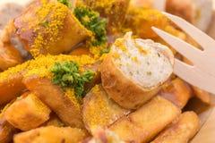 Currywurst met gebraden gerechten en een houten vork als heerlijke snack stock foto's