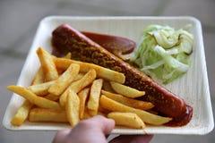Currywurst-Currywurst mit Pommes-Frites und Gurkensalat und -Tomaten-Ketschup Lizenzfreies Stockbild