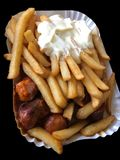 Currywurst & Pommes no fundo preto: Salsicha alemão famosa do caril do fast food com batatas fritas e molho de caril imagem de stock royalty free