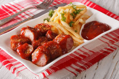 Currywurst sausage with french fries close-up. Horizontal Stock Photo