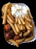 Currywurst y Pommes en fondo negro: Salchicha alemana famosa del curry de los alimentos de preparación rápida con las patatas f imagen de archivo libre de regalías