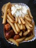 Currywurst y Pommes: Salchicha alemana famosa del curry de los alimentos de preparación rápida con las patatas fritas y la sals fotos de archivo libres de regalías