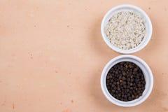 Curse la sal y los granos de pimienta grises en pequeños ramekins en el ti de Saltillo fotografía de archivo