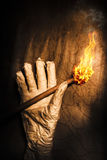 Curse of the tomb robber. Hand of a historic horror mummy holding a torch flame in a dark cursed tomb. Rise of the dead mummy Stock Images