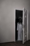 Cursed Horror Girl. Horizontal photo of a horrorful cursed girl looking from the door. Her hair covering her face, she looks creepy. Horror concept. She wears a Stock Images