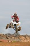 Curseur de motocross d'ATV au-dessus d'un saut Photographie stock libre de droits
