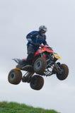 Curseur de motocross d'ATV au-dessus d'un saut Images stock
