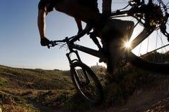 Curseur de vélo de montagne dans le coucher du soleil Photos stock