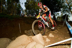 Curseur de XCO dans la section rocheuse à la coupe du monde d'UCI MTB Image libre de droits