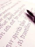 Cursivo de los it3alicos y pluma de la tinta de la caligrafía en el papel Foto de archivo