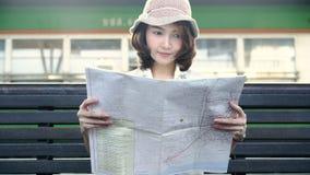 Curso asiático da mulher do mochileiro do viajante em Banguecoque, Tailândia Sentido fêmea novo feliz e vista no mapa de lugar no video estoque