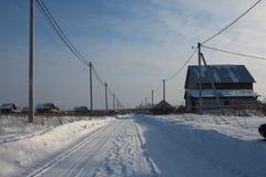 Curso cancelado inverno da estrada entre os montes de neve no inverno na vila Siberian foto de stock royalty free