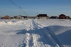 Curso cancelado inverno da estrada entre os montes de neve no inverno na vila Siberian fotos de stock