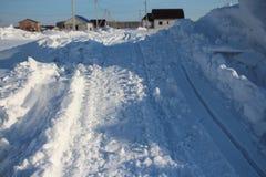 Curso cancelado inverno da estrada entre os montes de neve no inverno na vila Siberian imagem de stock royalty free