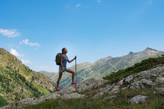 Curso da jovem mulher com a trouxa na montanha Foto de Stock