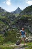 Curso da jovem mulher com a trouxa na montanha Imagem de Stock