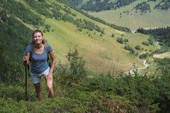 Curso da jovem mulher com a trouxa na montanha Fotografia de Stock