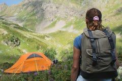 Curso da jovem mulher com a trouxa na montanha Foto de Stock Royalty Free