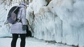 Curso da mulher no gelo do Lago Baikal Viagem à ilha do inverno A menina está andando no pé de rochas do gelo O viajante olha filme
