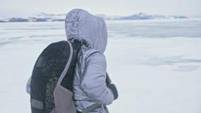 Curso da mulher no gelo do Lago Baikal Viagem à ilha do inverno A menina está andando no pé de rochas do gelo O viajante olha vídeos de arquivo
