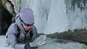 Curso da mulher no gelo do Lago Baikal Viagem à ilha do inverno A menina está andando no pé de rochas do gelo O viajante olha video estoque