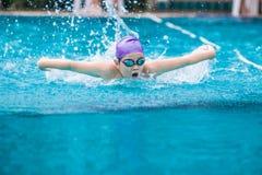 Curso de borboleta da natação do nadador do menino em um p nadador claro agradável Imagem de Stock Royalty Free