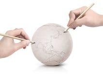 Curso de duas mãos que tira o mapa de Ásia na bola de papel Fotos de Stock Royalty Free