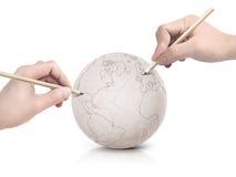 Curso de duas mãos que tira o mapa de América na bola de papel Fotografia de Stock