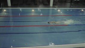 Curso de rastejamento de flutuação do nadador profissional fêmea na piscina do luxo da água video estoque
