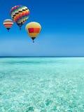 Curso dos balões de ar quente sobre o mar fotografia de stock royalty free