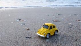Curso e f?rias Carro amarelo do brinquedo na praia contra o mar