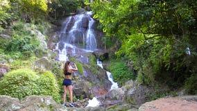 Curso e tecnologia Jovem mulher no sportswear que toma a foto da cachoeira grande em seu smartphone filme