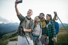 Curso, turismo, caminhada e conceito dos povos - grupo feliz de amigos que tomam o selfie e a caminhada foto de stock