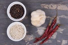 Cursus grijs zout, peperbollen, de droge Spaanse pepers van de knoflookadvertentie op gr. Stock Foto