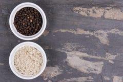 Cursus grijze zout en peperbollen in kleine ramekins op grijze lei Stock Foto's